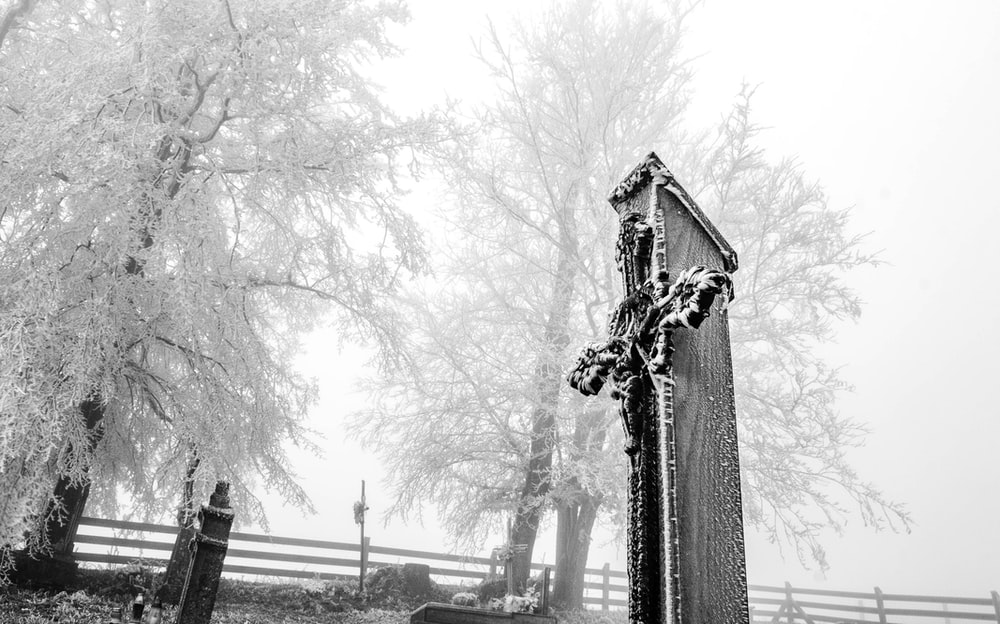 grayscale photo of cross tombstone