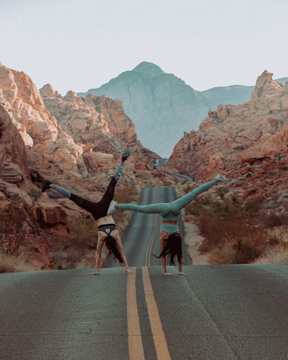 woman doing handstand on asphalt road