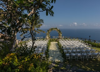 white chairs and green and white floral arch