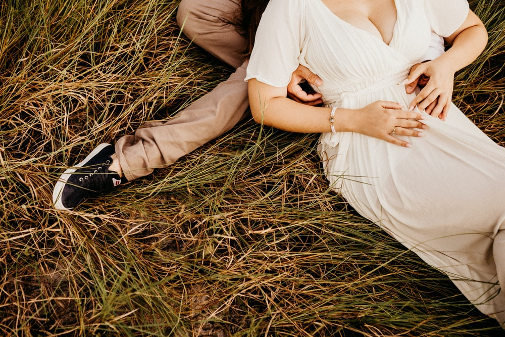 woman wearing white dress laying on man