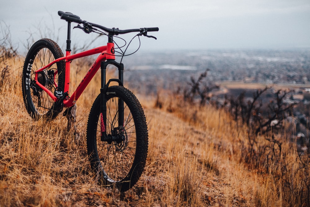 red and black hardtail bike on brown grass field