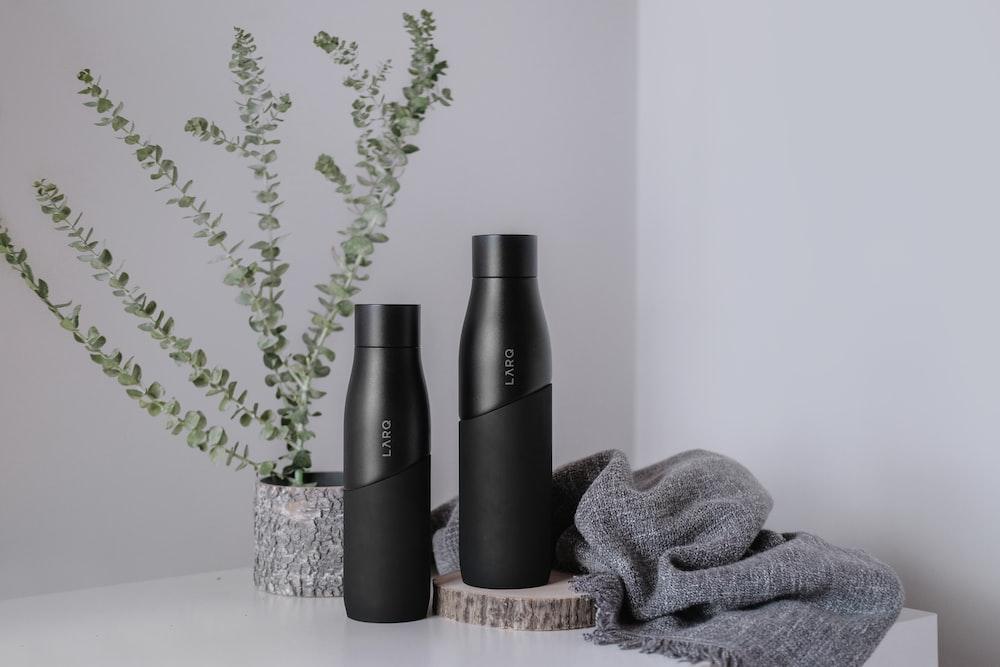 two black plastic bottles beside gray textile on table