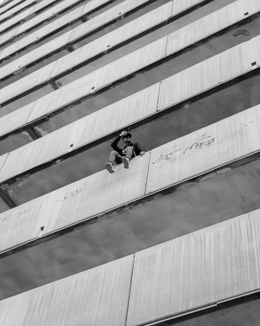 grayscale photography of unknown person sitting on wall