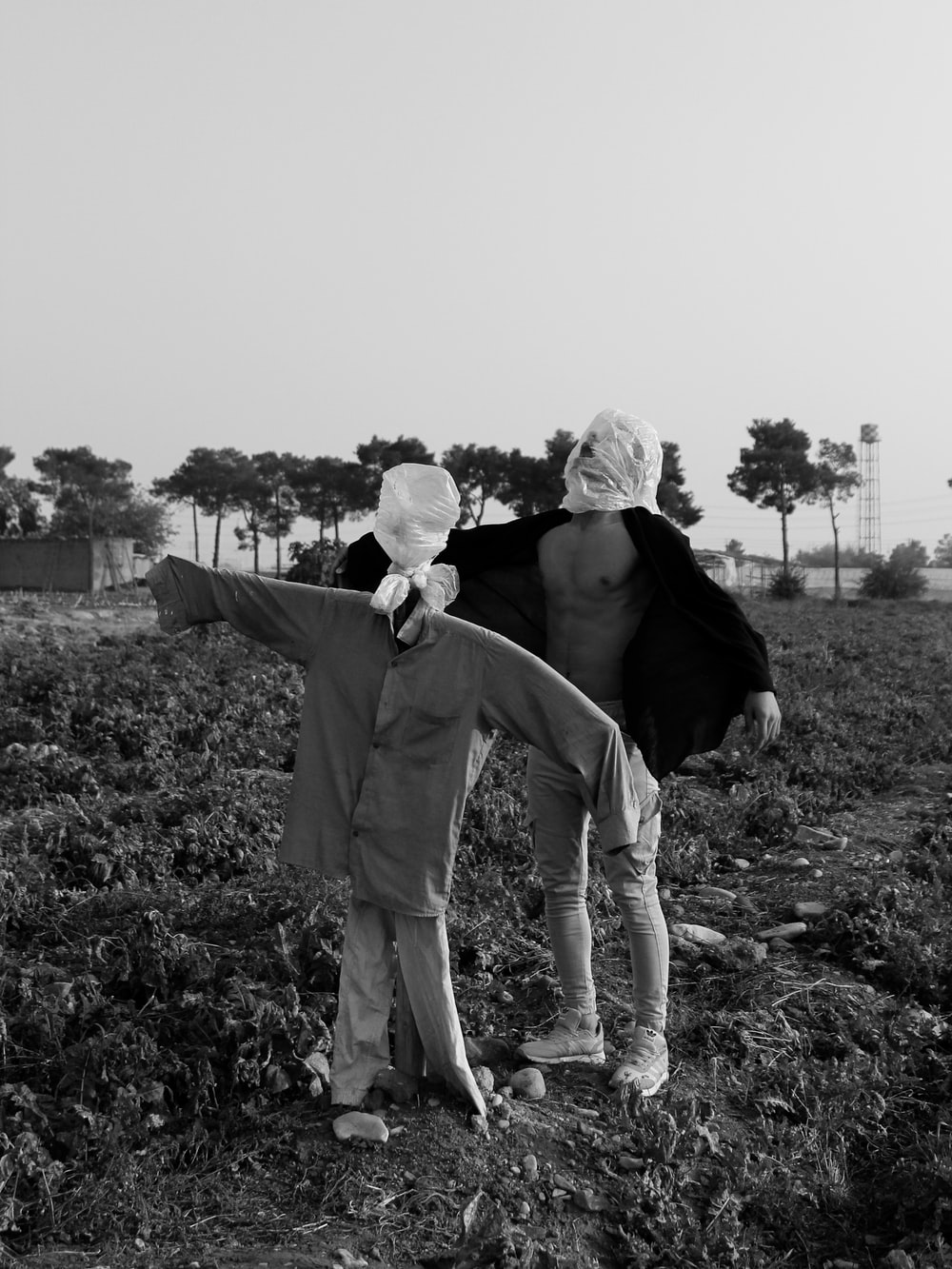 grayscale photography of man standing beside scarecrow