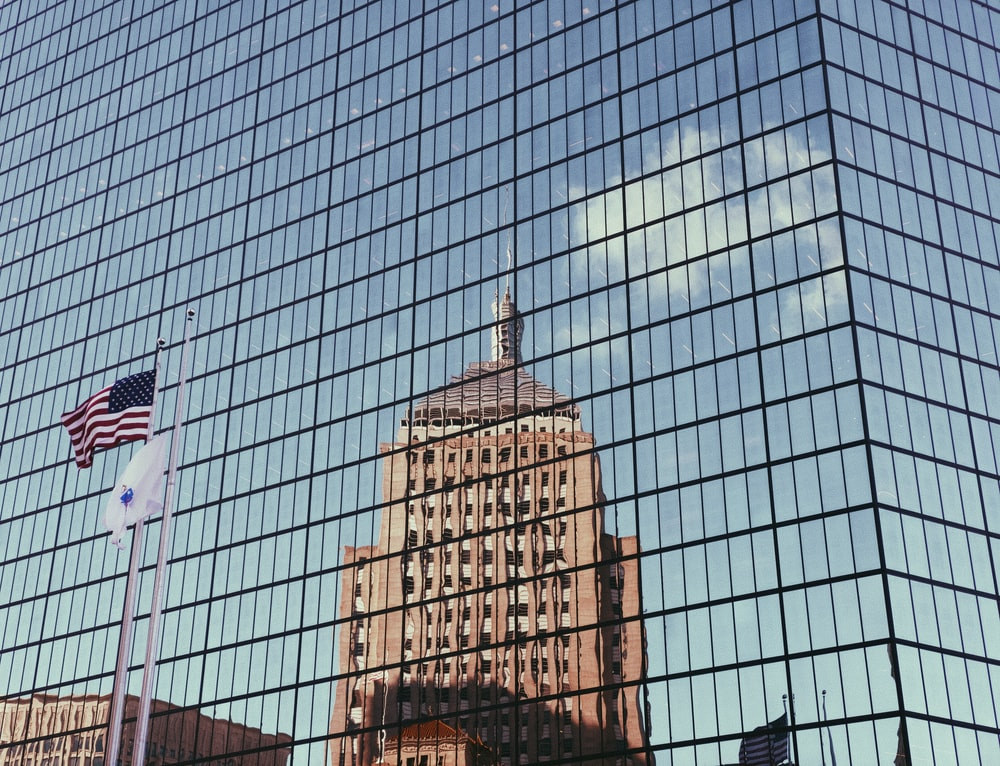 reflection on brown building on glass building