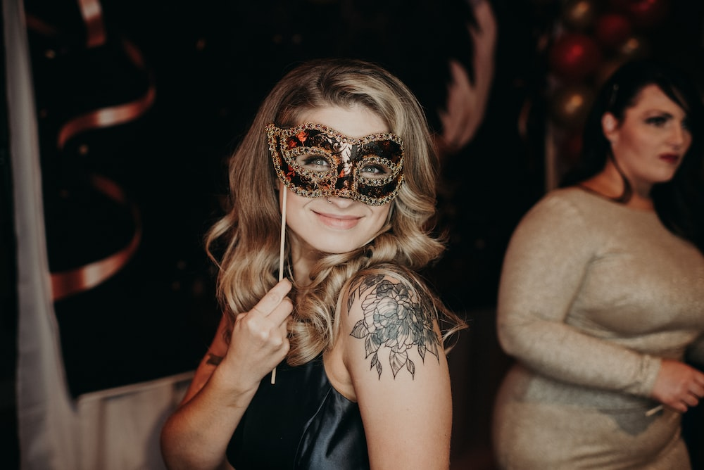 woman wearing black dress and black and gold mask