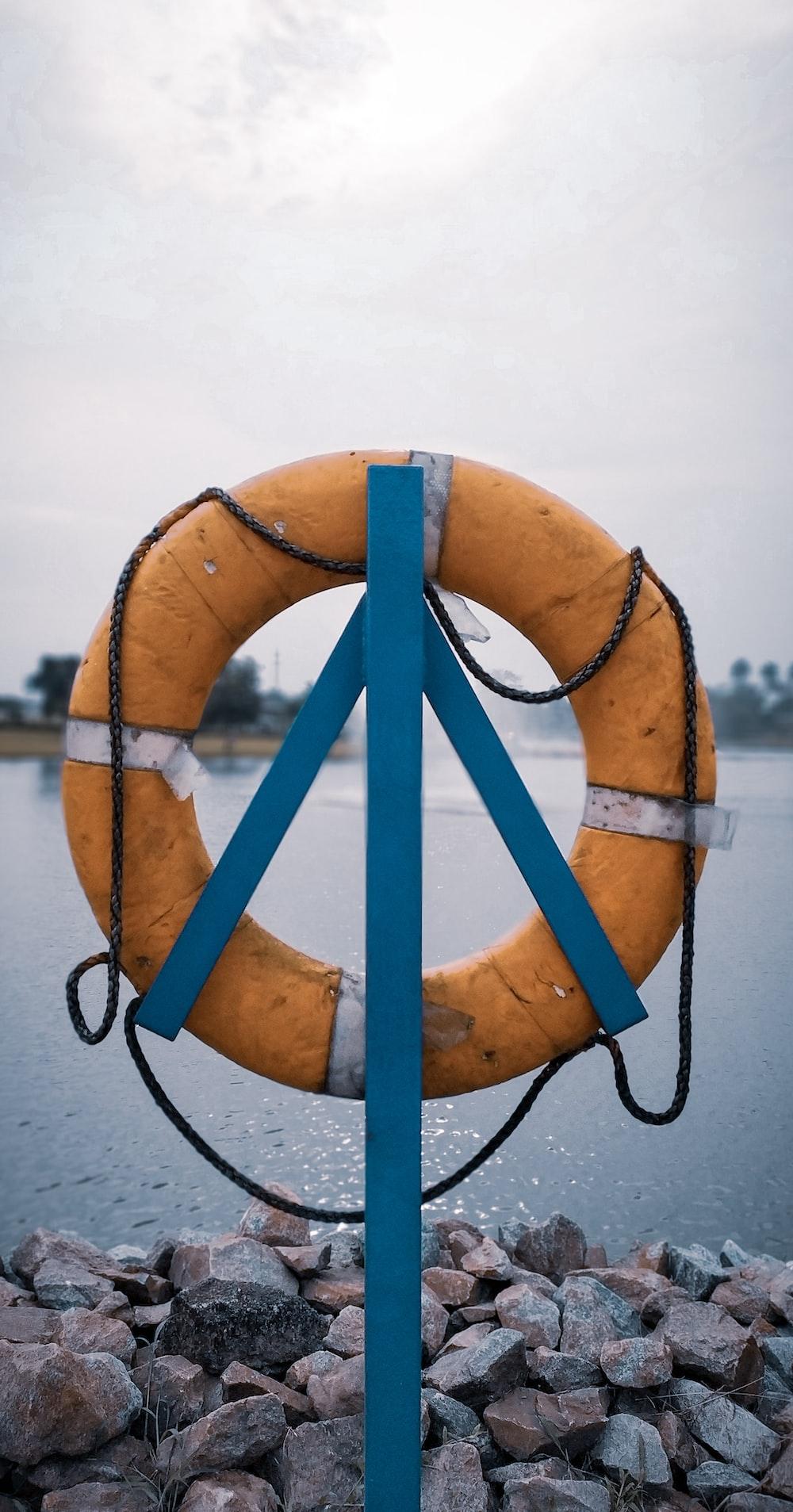 orange lifebuoy hanging on post near water