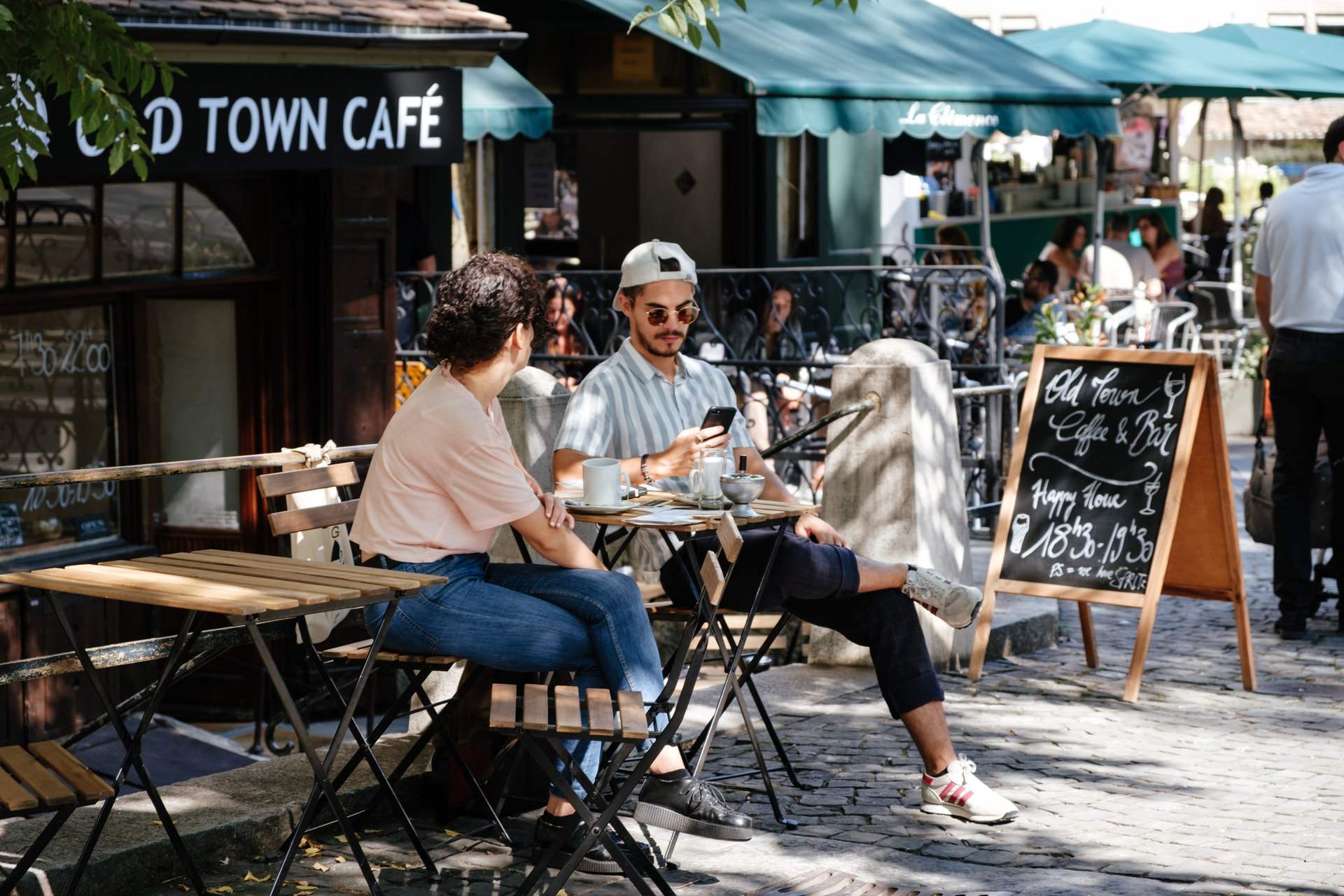 man and woman sitting in front of folding table in front of cafe with green awnings