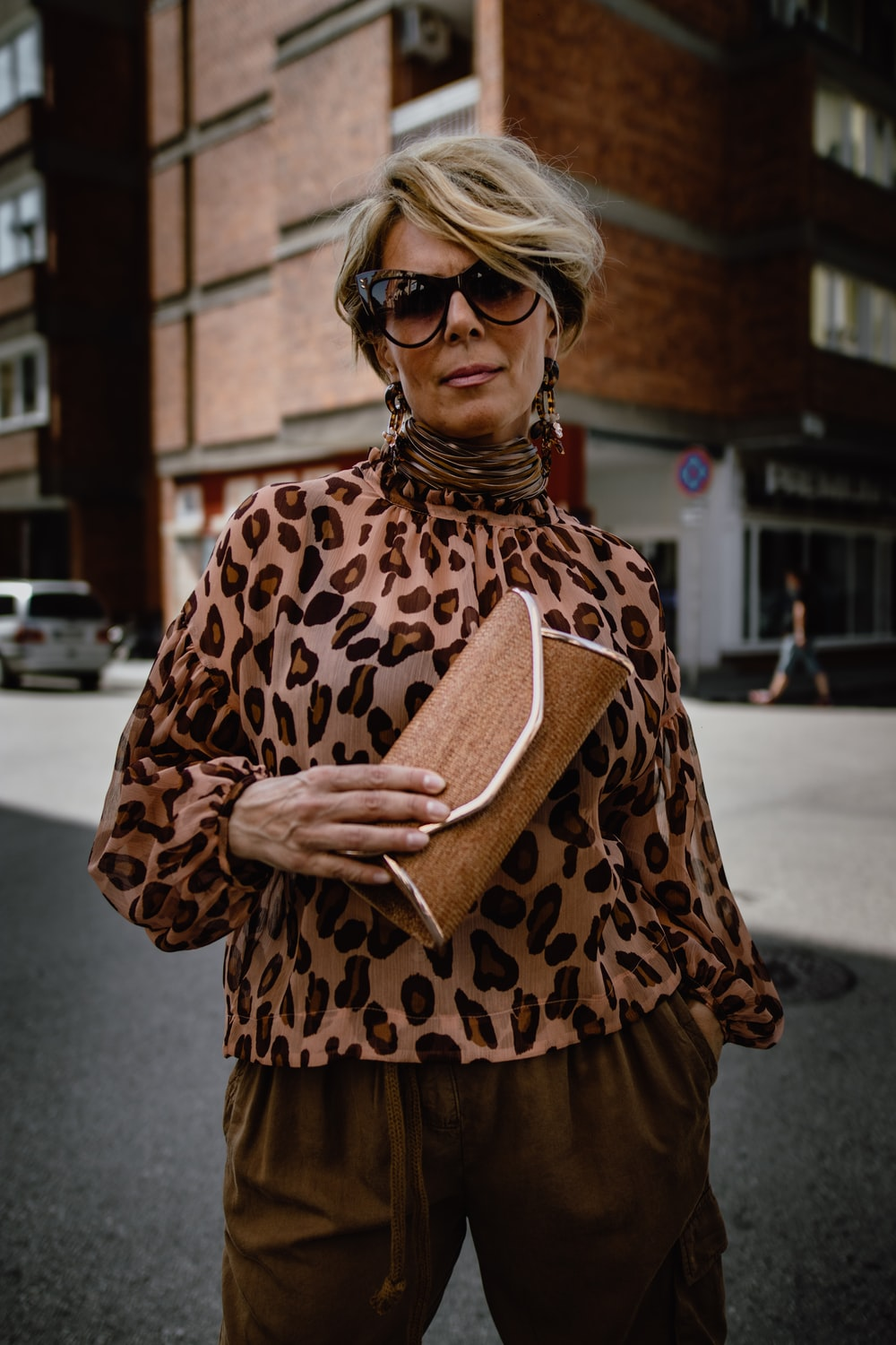 woman wearing brown leopard long-sleeved blouse holding brown pouch standing