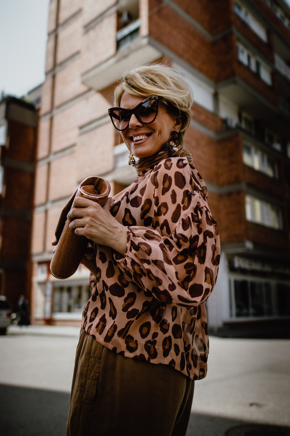 woman wearing brown and beige blouse holding brown pouch bag