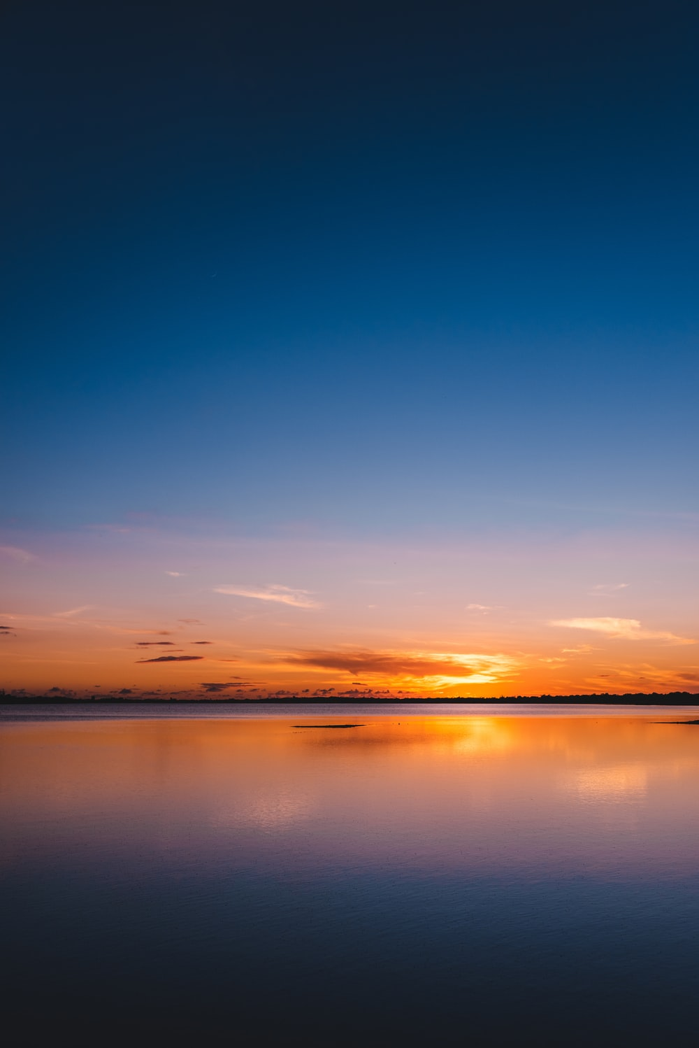 orange and blue sky with calm body of water