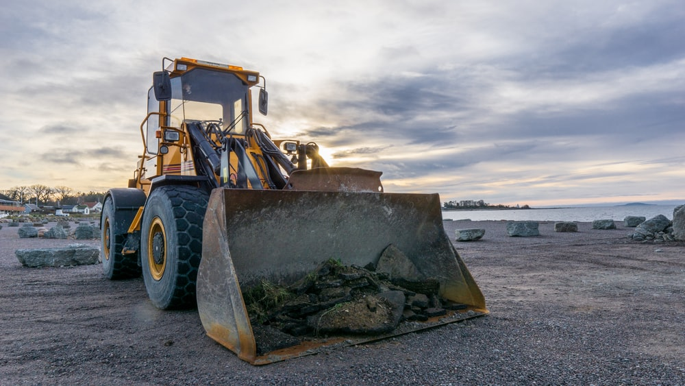 shallow focus photo of yellow front loader