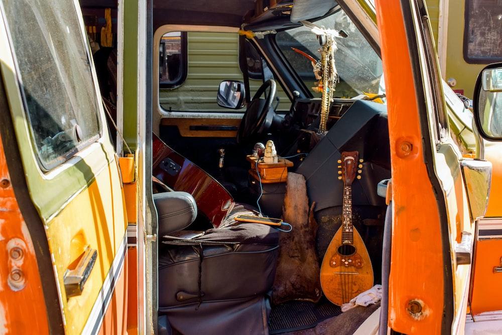 brown acoustic guitar on black car