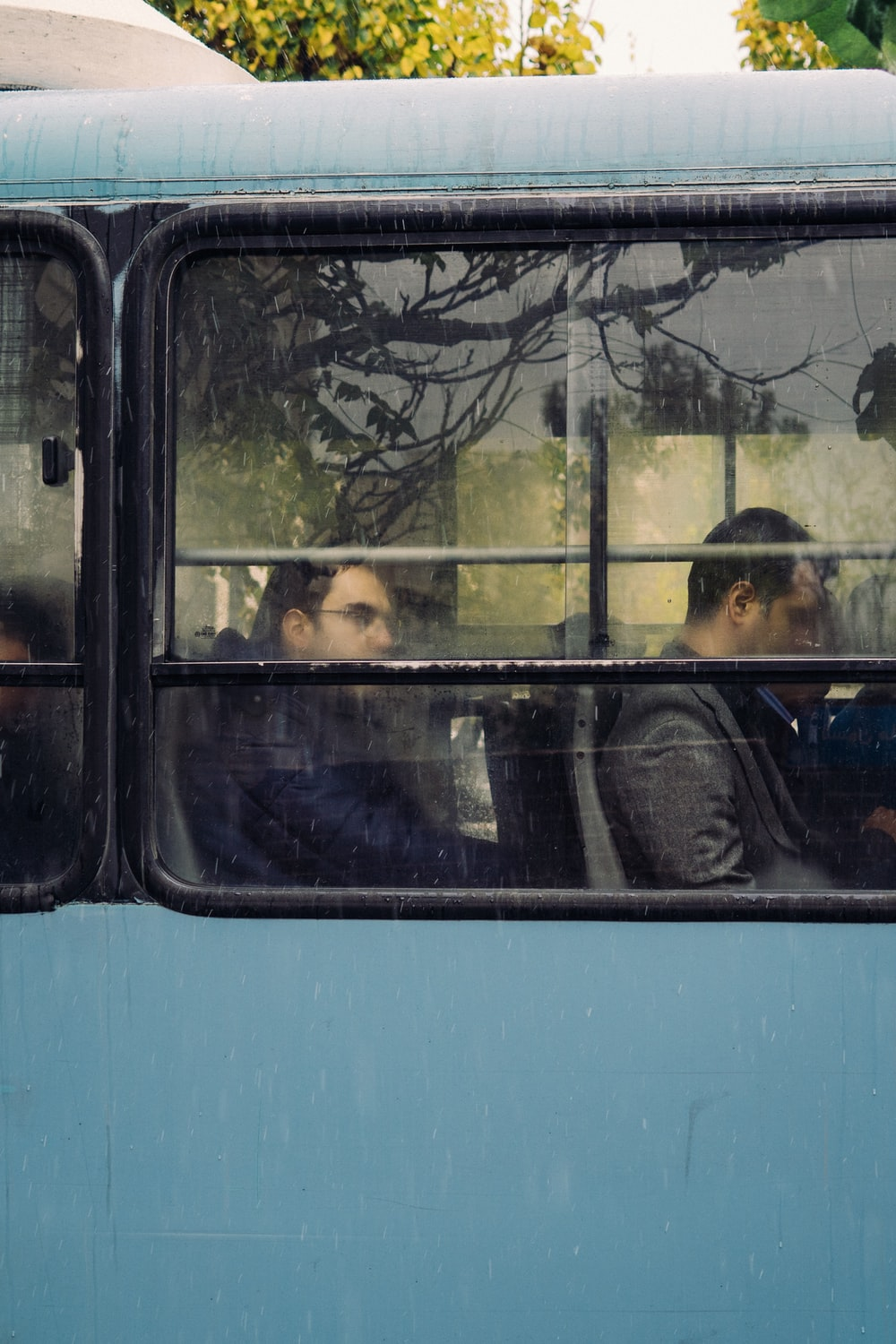 people sitting in blue bus during daytime