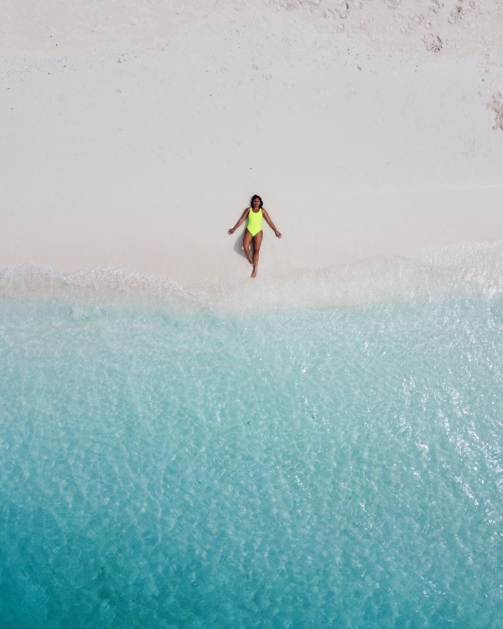 woman wearing green one-piece swimsuit sunbathing near seashore