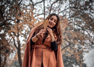 woman wearing brown coat holding brown leaf