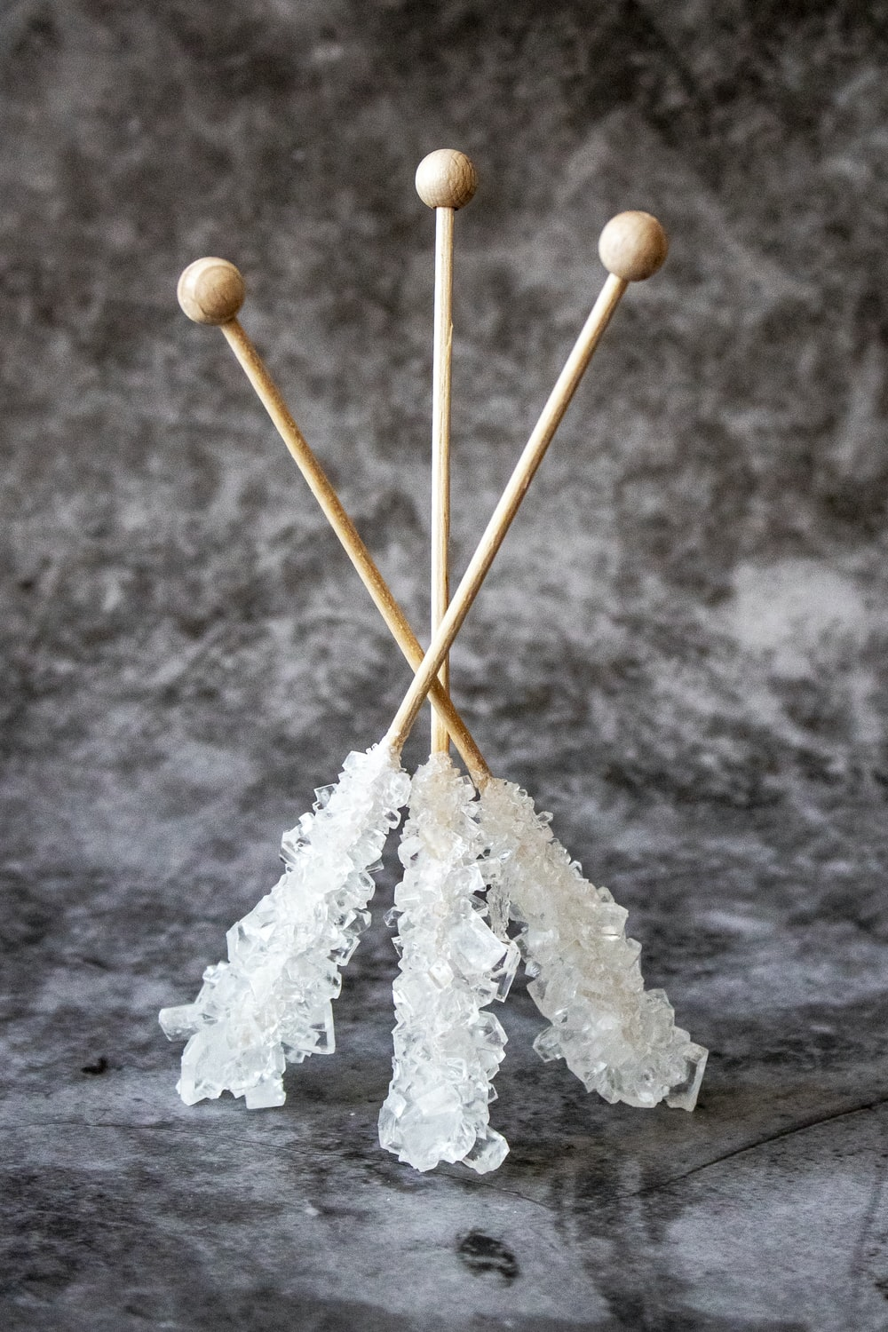 three brown wooden sticks with quartz