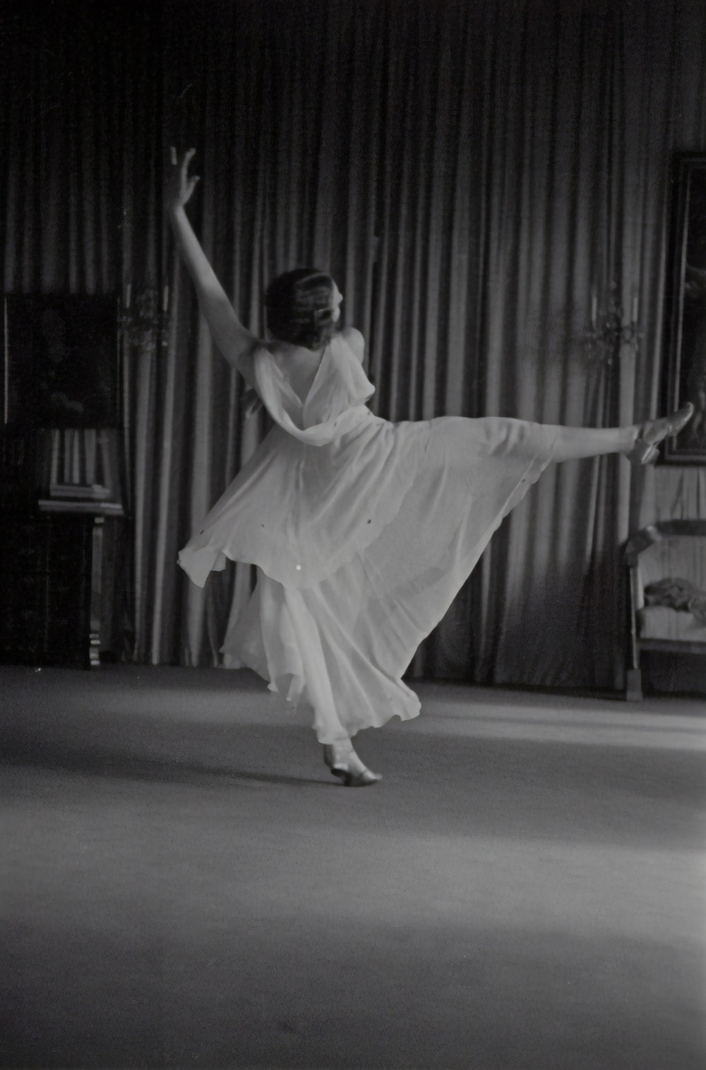 grayscale photo of woman dancing near curtains