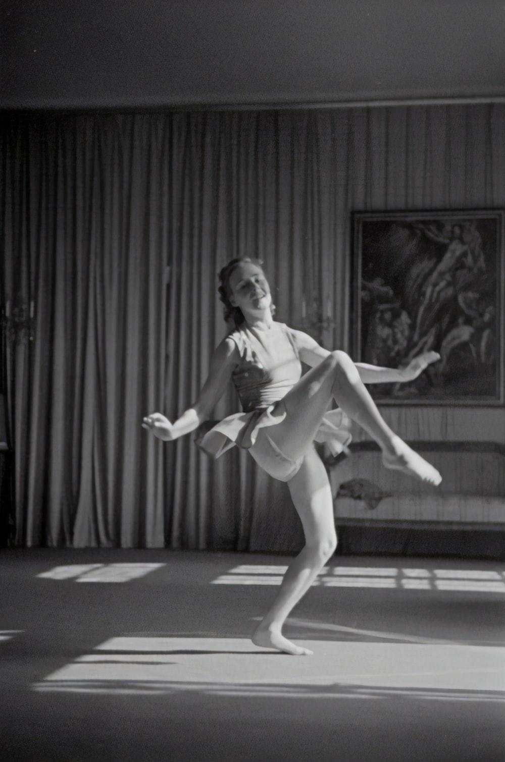 grayscale photo of woman dancing near curtain