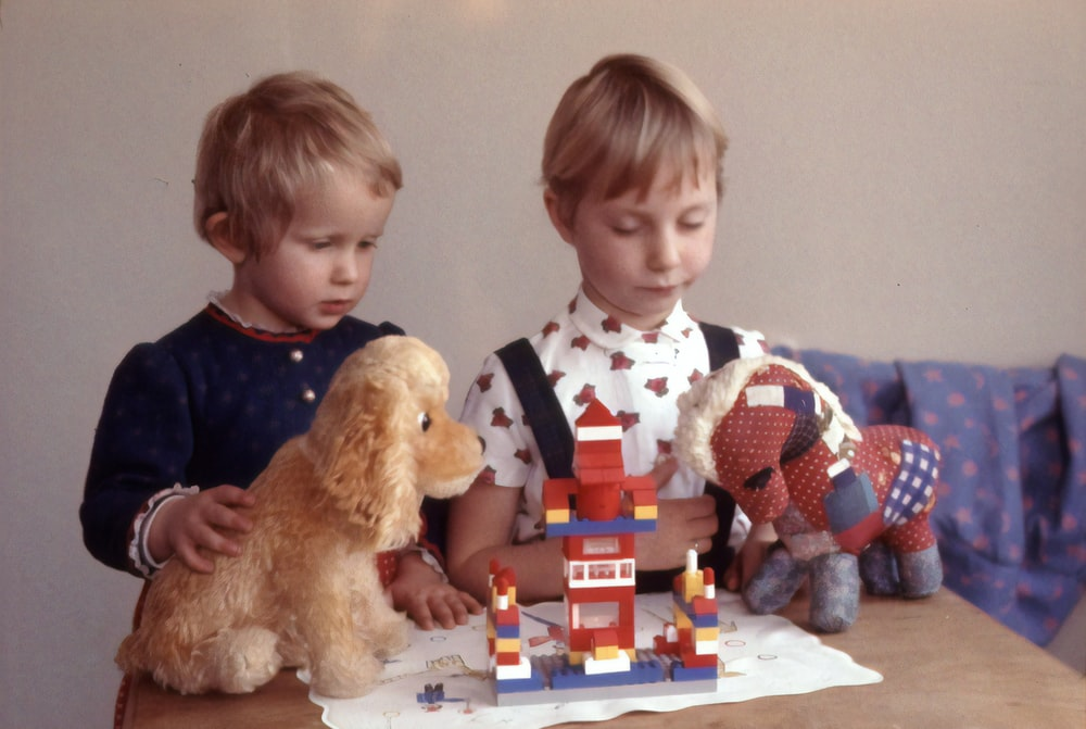 two children playing toys on table