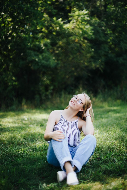 woman in blue jeans sitting on grass field