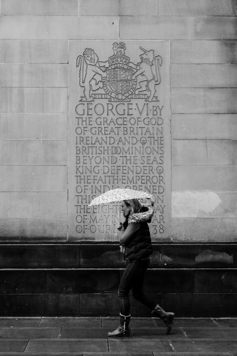 grayscale photo of woman with umbrella walking on street