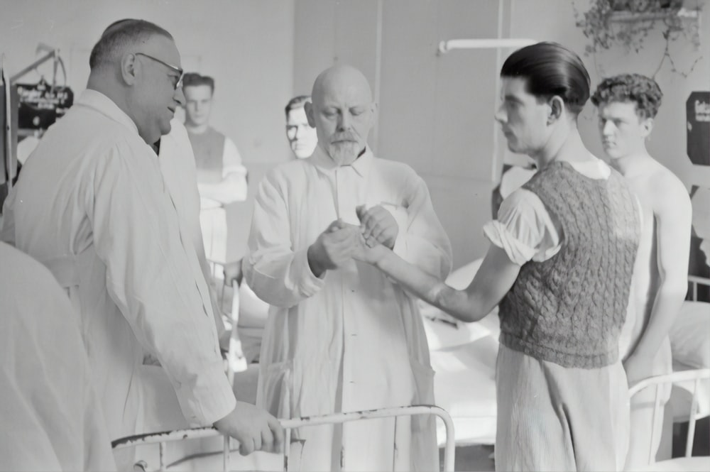grayscale photography of man in lab gown