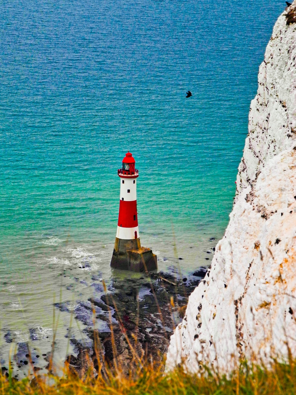 white and red lighthouse near ocean