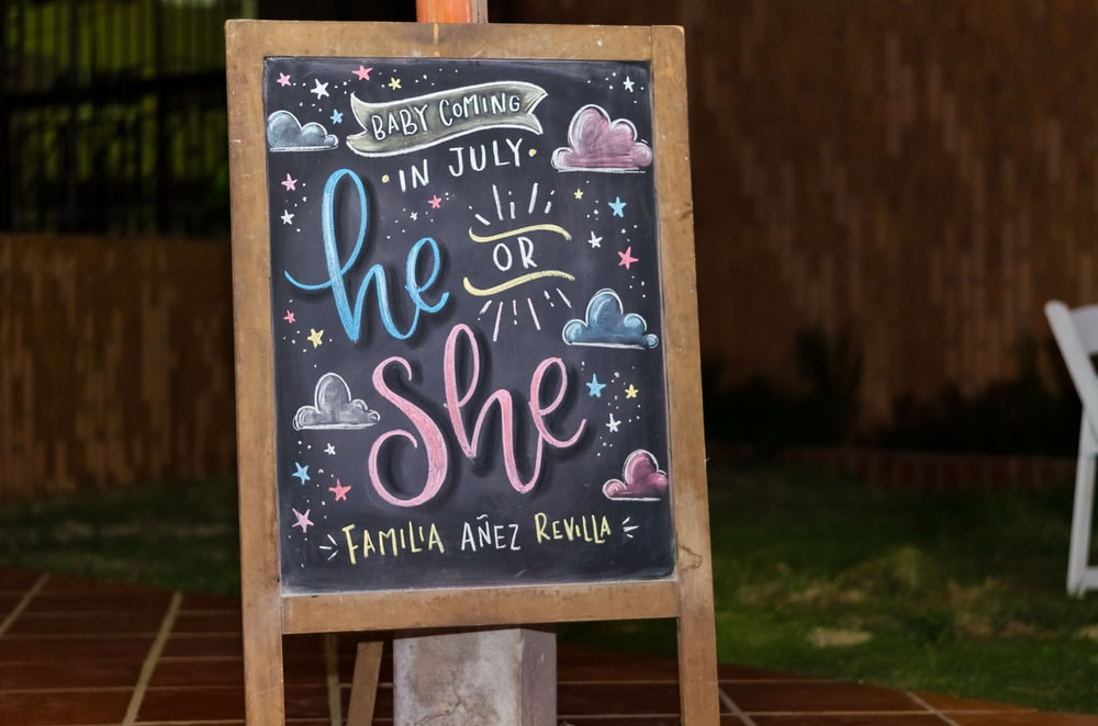 brown framed chalkboard easel with baby coming in July he or she text