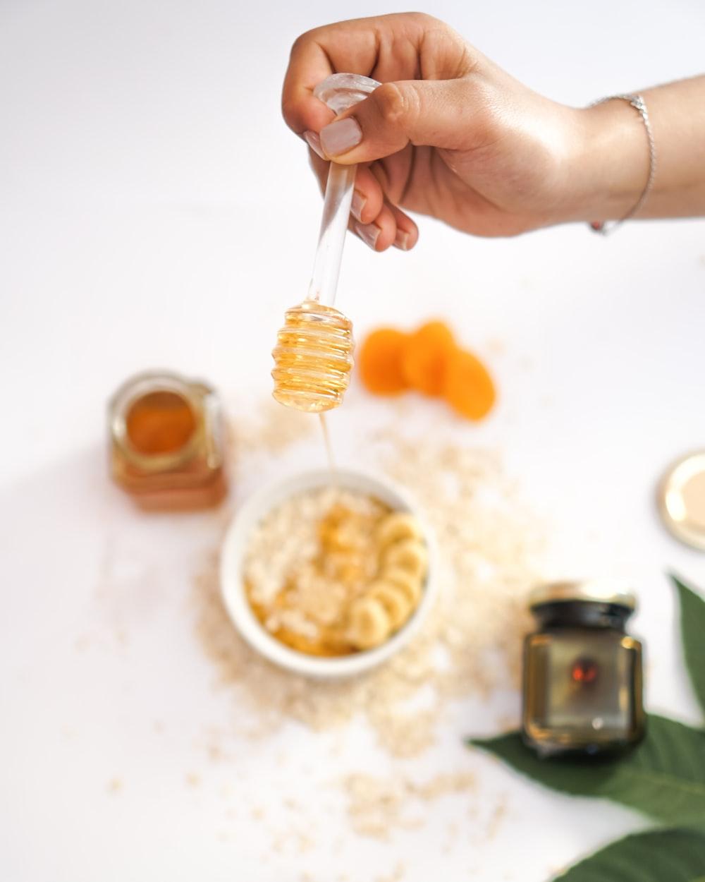 person holding honey ladle