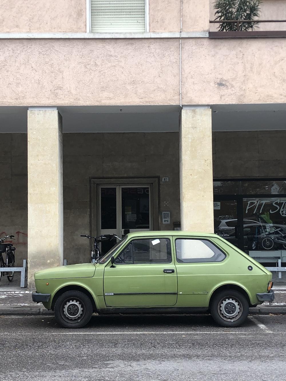 green vehicle near white house