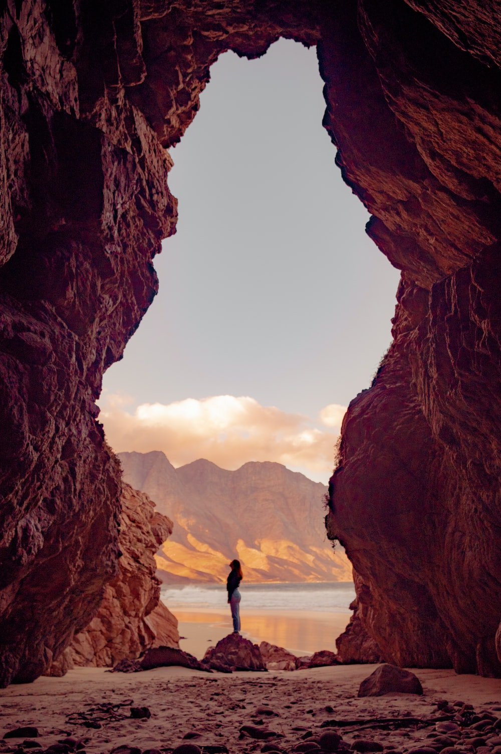 silhouette of person standing on top of rock during daytime