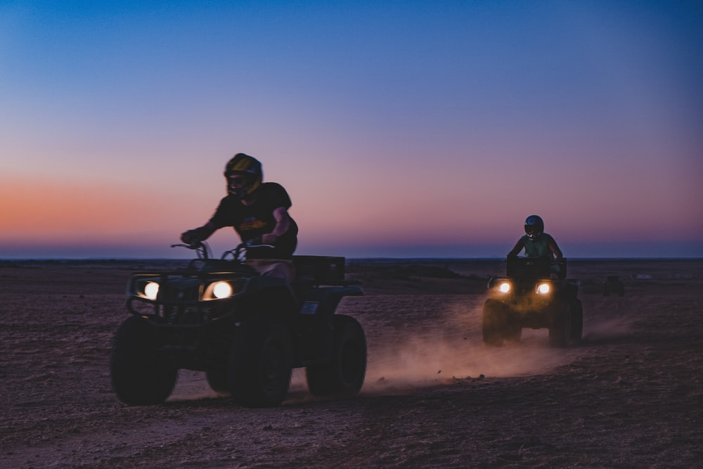 two persons on all-terrain vehicles