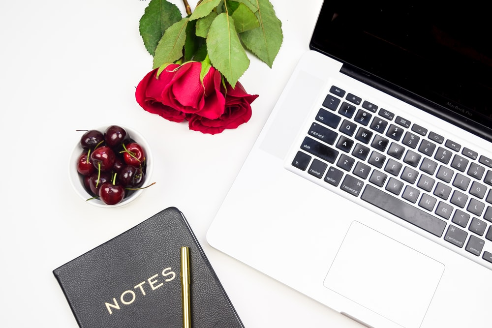 flatlay photo of rose, MacBook Pro, cherries, and black notebook
