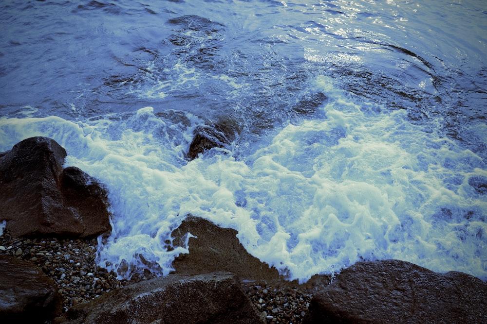 wave splashing on rocks during daytime