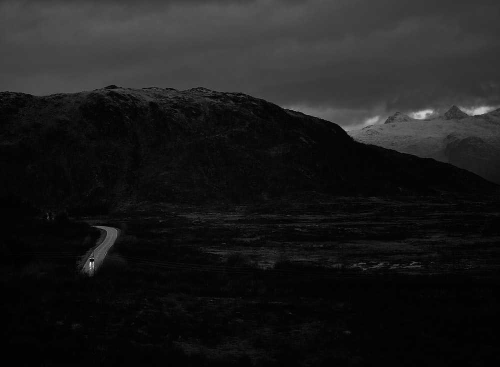 grayscale photography of cars on road by mountain under white skies