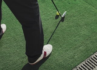 person holding golf club about to swing ball on grass at daytime