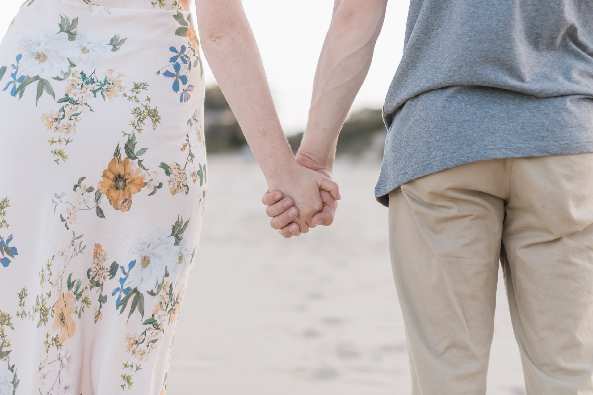 man and woman holding hands on sand field