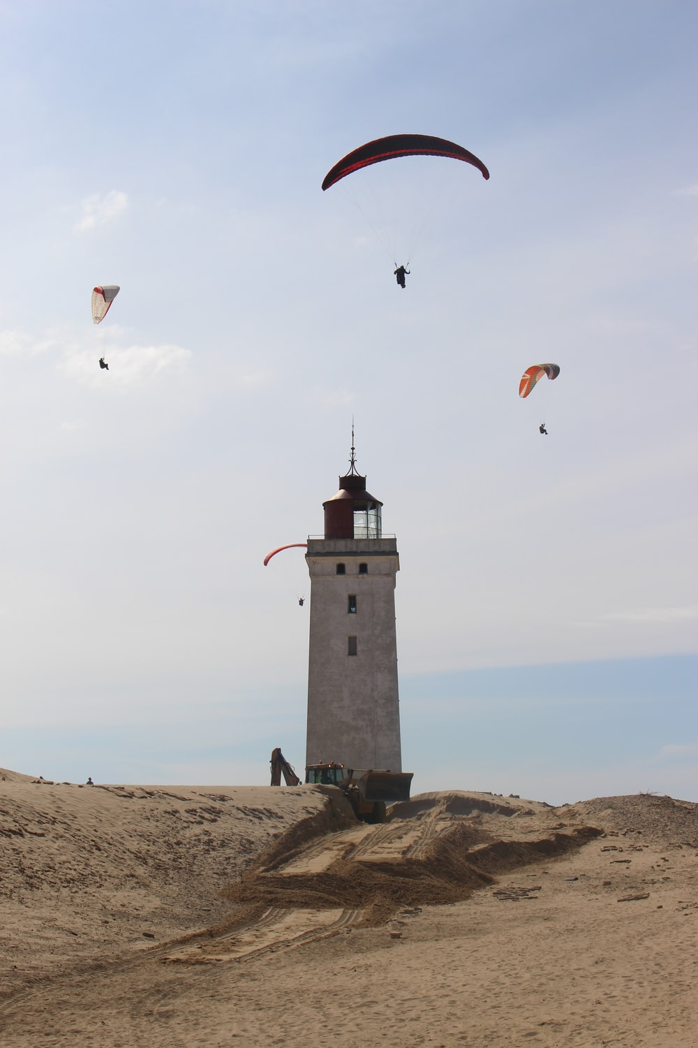people paragliding above white and black lighthouse under white and blue sky