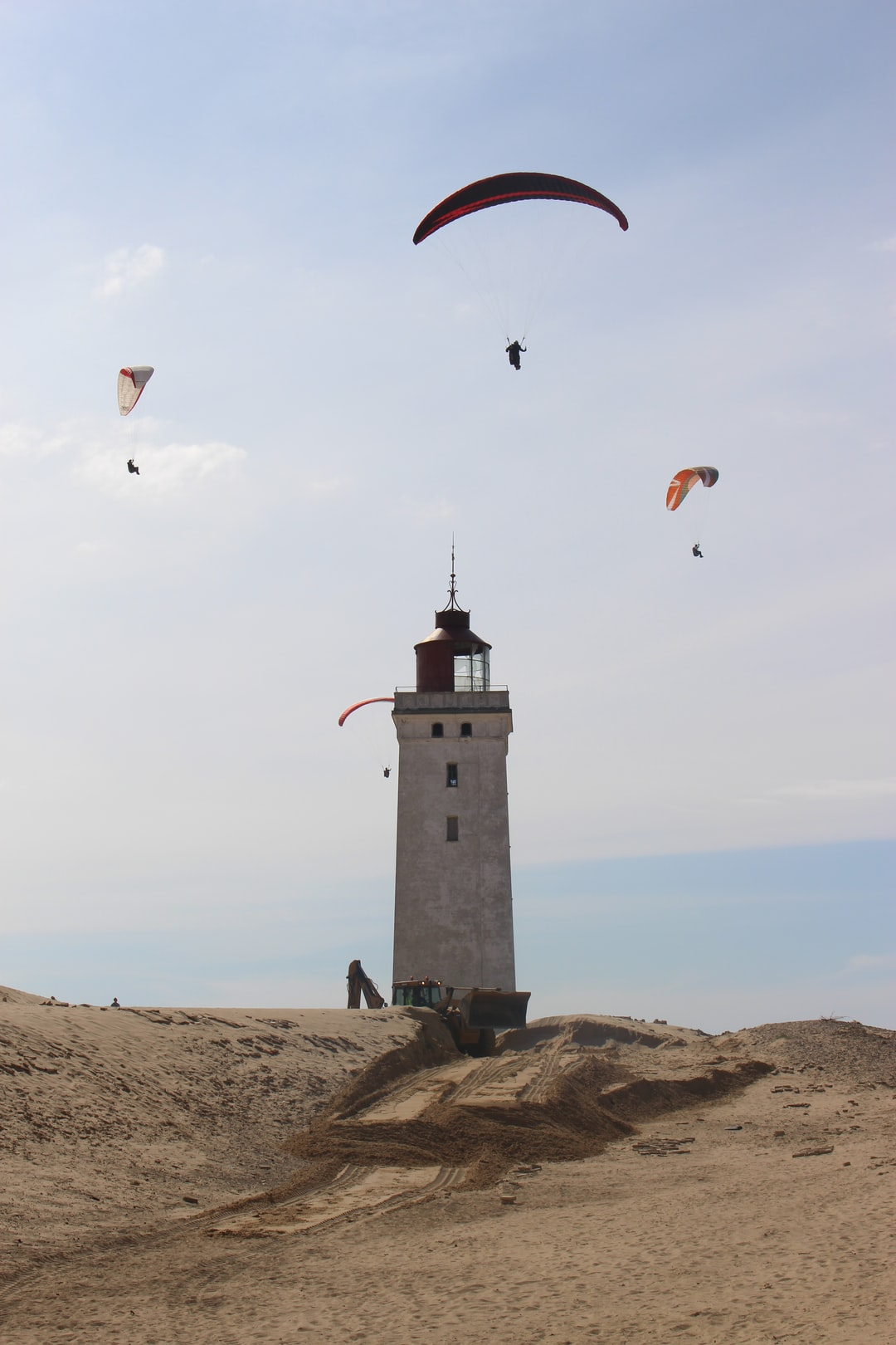Lighthouse and paragliders in North Jutland, Denmark, Scandinavia, Europe: The Rubjerg Knude fyr is located amidst a huge shifting dune. Photographed in 2017. In october 2019 the lighthouse was rescued and was set 70 meters into the inland. It was in grave danger of falling into the sea. At the photo first preparatory works are to be seen.