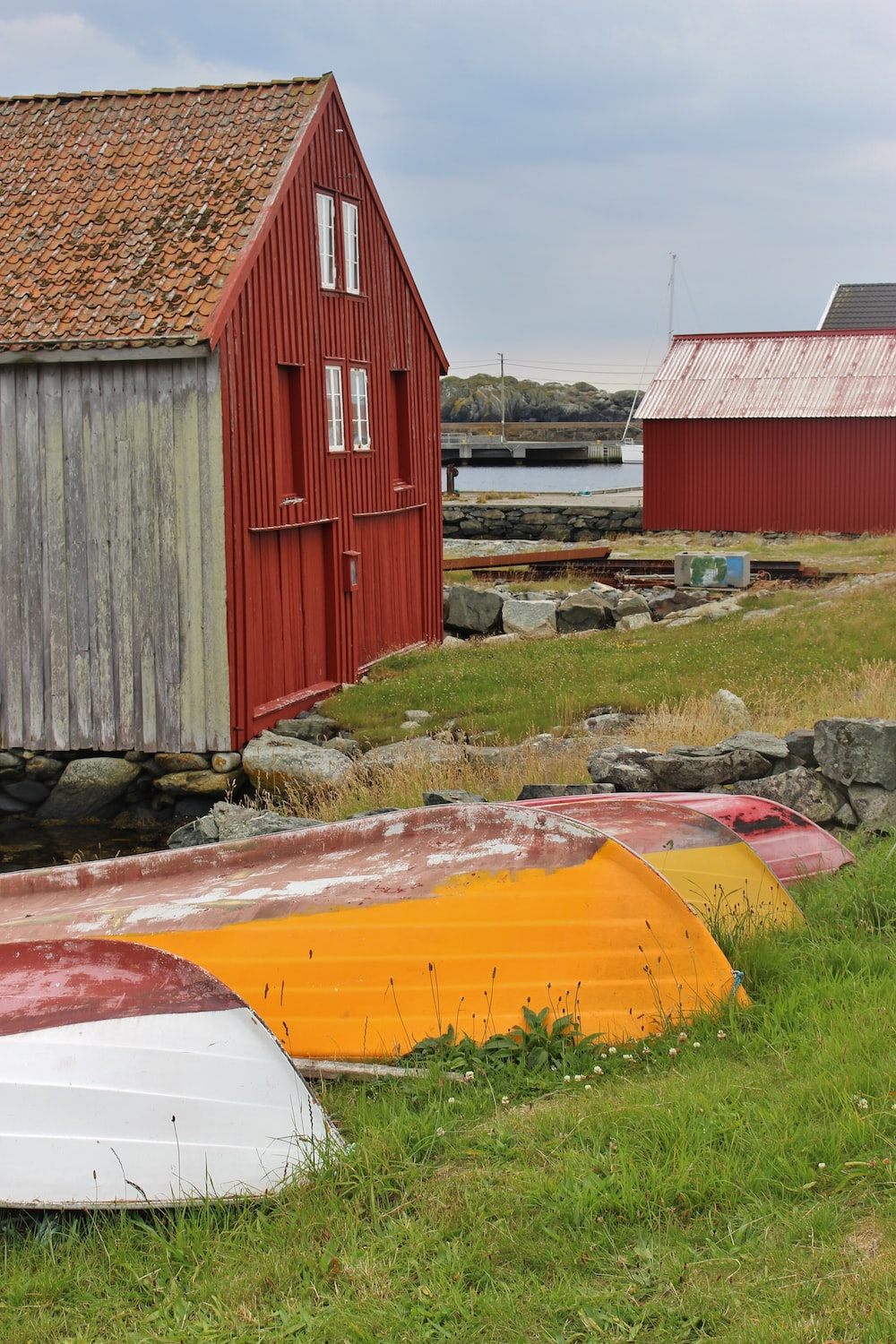 boats and buildings on grass field during day
