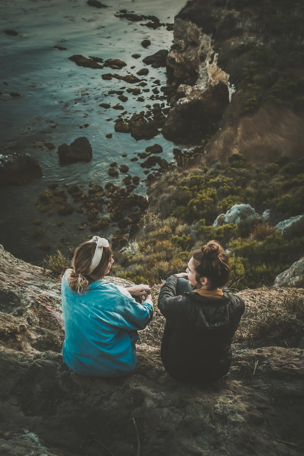 two women sitting on cliff while chatting viewing blue body of water