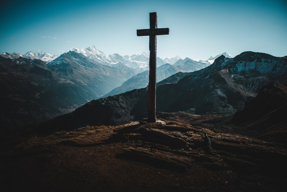 cross on rocky mountain during day