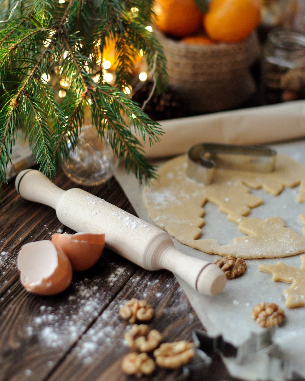 white wooden rolling pin near dough, egg shell, orange fruits, and walnuts
