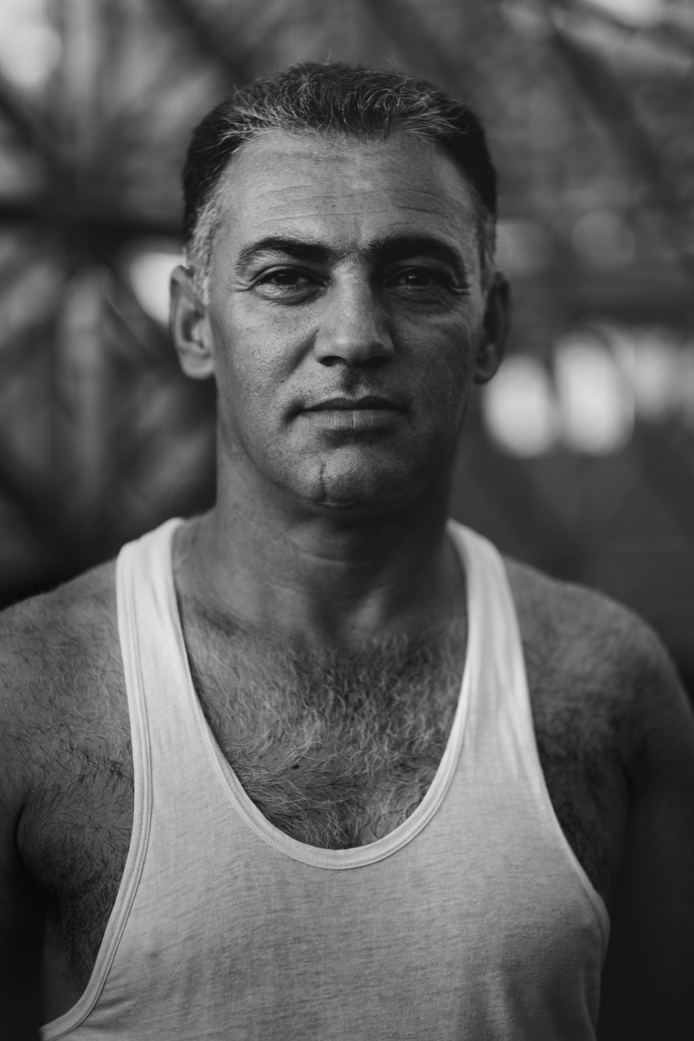 grayscale photography of man wearing tank top standing