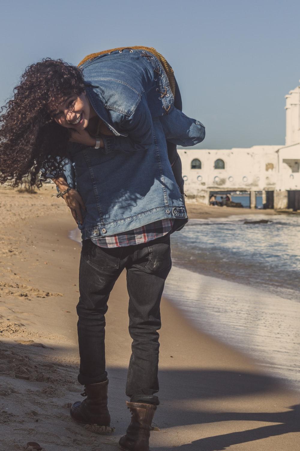 man carrying woman walking on seashoire