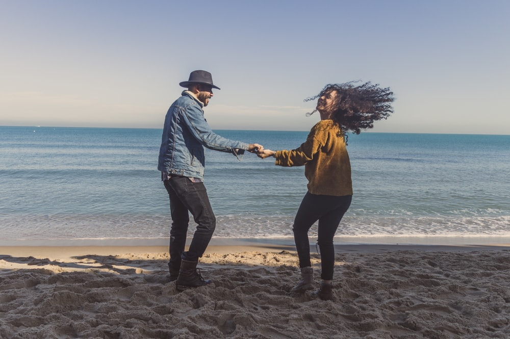 man and woman standing on seashore