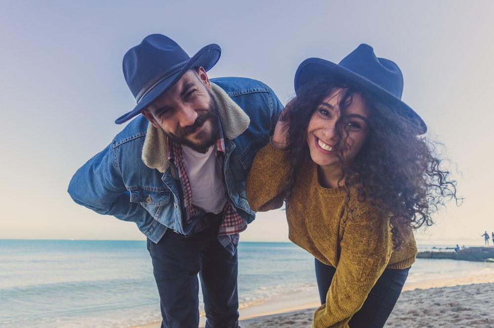 smiling man and woman wearing black cowboy hats