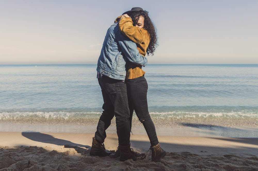 hugging man and woman on seashore