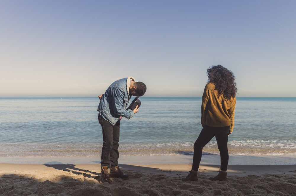 man bowing in front of a woman on seashore during day